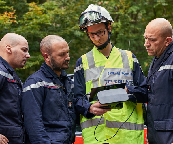 A drone pilot showing emergency services what they see on their tablet connected to their remote control