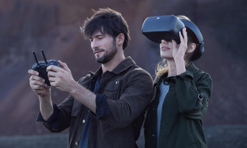 A man flying a drone with a woman using the DJI goggles
