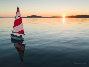 1 person boat with a sail at sun set on a lake